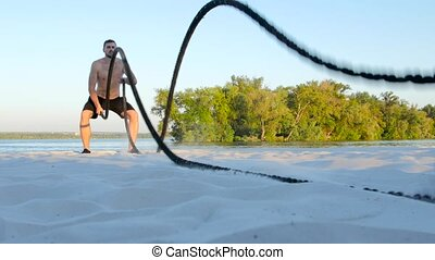 Sports man conducts training with the ropes on the sandy shore