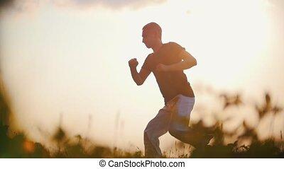 Sports man dancing capoeira on a background of amazing sunset, sun glare, summer