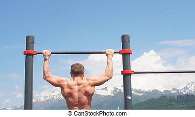 Sports man doing pull-up exercise on a horizontal bar...