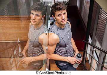 Sports man holding bottle with water and resting in gym