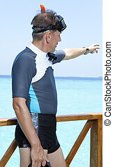 sports man in equipment for a snorkeling on sundeck shows a hand in the sea. Maldives