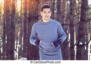 Sports man jogging in forest. Winter.