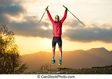 Sports man makes a jump in the mountains during a sunset