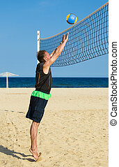 Sports man plays in beach volleyball