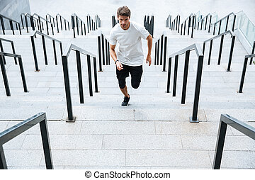 Sports man running by ladder at the stadium