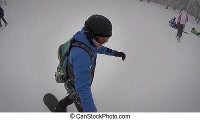 Sports man, warmly dressed in sports gear, rapidly rolling down the slope, doing small tricks in snowy weather, it is not afraid to fall