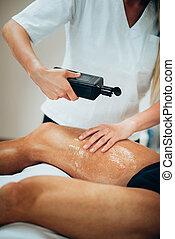 Sports massage. Therapist pouring massage oil