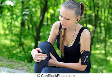 Sports Park - Sportswoman bended knee because of an ankle...