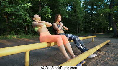 sports people krosfit. Two slim girls doing exercises in the park on the playground.