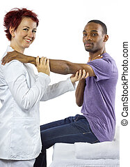 Sports Physical Therapy - young female therapist helping...