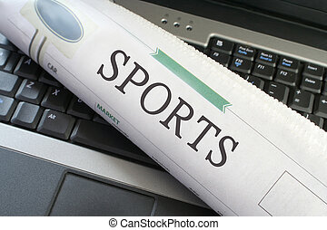 Sports headlines section of the newspaper laying on a laptop