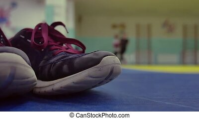 Sports shoes are on the mats in the gym. In the background ...