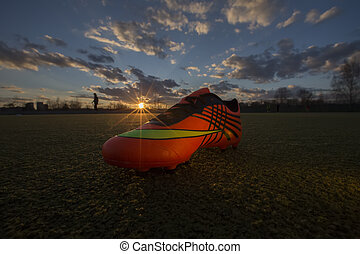 Sports shoes on the background of the field at sunset. Football field with sneakers