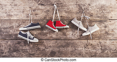 Sports shoes on the floor - Three pairs of sneakers hang on ...