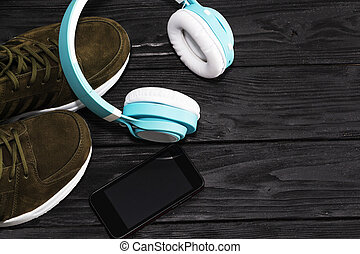 Sports shoes, smartphone and headphones on wooden black background. Playing sports, running.