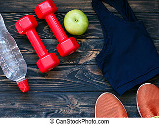 Sports sneakers, dumbbells, drinking clean water, on the background