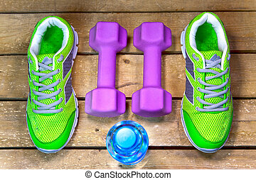 Sports sneakers, dumbbells, drinking water on a wooden background