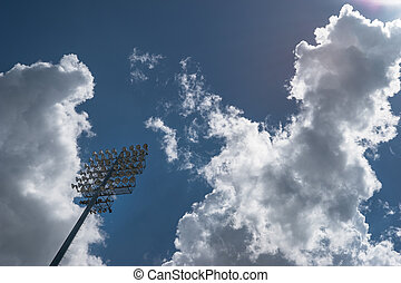 Sports stadium lights against a partially cloudy sky