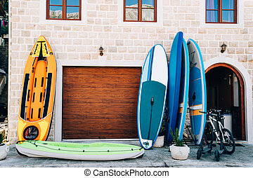Sports travel equipment rental store - rubber boats, inflatable canoes and kayaks, gliding boards, bicycles and electric scooters. A building with a garage and brown windows, made of white stone