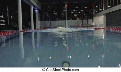Sports woman floating breaststroke style in blue water...