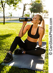 Sports woman in park holding bottle with water.