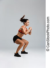 Sports woman make sport exercises isolated indoors.