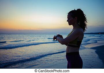 sports woman on ocean coast in evening using smart watch