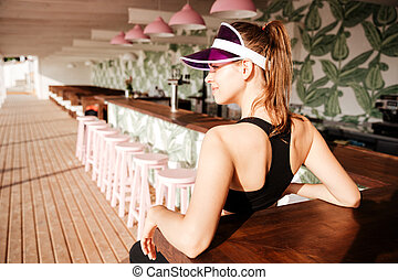 Sports woman resting after workout in a beach cafe