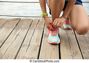 sports woman runner tying shoelace on wooden boardwalk ...