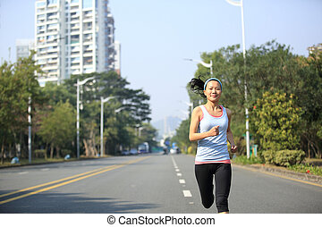 sports woman running on city road