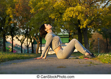 Sports woman sitting in park relaxing