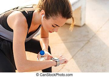 Sports woman sitting outdoors listening music