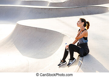 Sports woman sitting outdoors listening music
