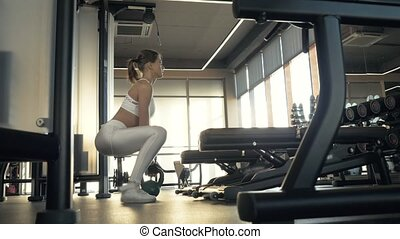 Sports woman squatting with weight for training muscle legs...