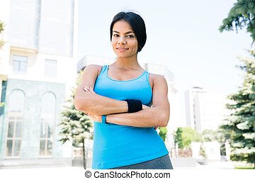 Sports woman standing with arms folded outdoors