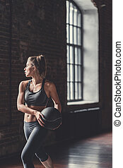 Sports woman with a ball indoors