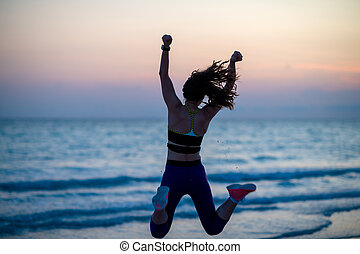 sports woman with open arms rejoicing on beach in evening