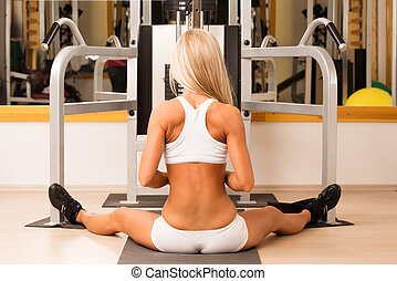 Sports young woman doing exercises in gym