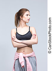 Sports young woman standing with arms folded and looking away