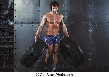Sportsman athlete crossfit man working out exercising with a tires powerlifting lifestyle bodybuilding concept.