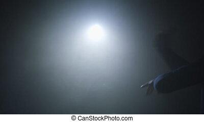 Sportsman boxing in smoky studio. Silhouette on a dark...