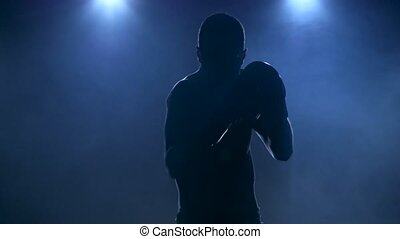 Sportsman boxing in smoky studio. Silhouette on a dark background