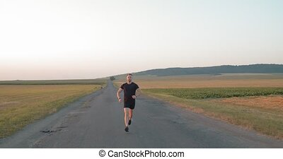 Young sportsman in black t-shirt, shorts and sneakers doing cardio on asphalt road among green fields. Strong man training on nature during sunset.