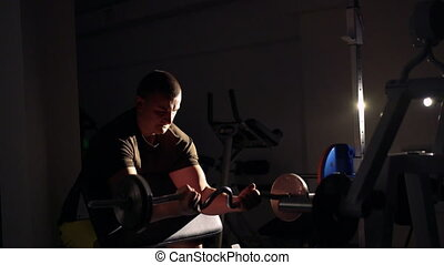 Sportsman doing exercise with barbell for biceps in the gym 4k