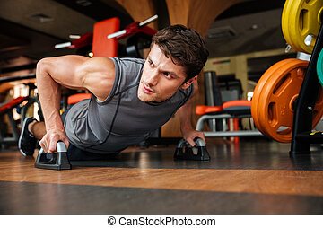 Sportsman doing push-up exercises in gym - Handsome young...