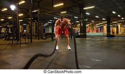 Sportsman exercising with ropes - Young man in shorts...