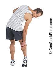 Sportsman feeling pain in his calf. Touching his leg