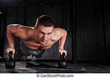 sportsman, görande push-ups, övning, med, kettlebell, in, a, crossfit, genomkörare, mot, tegelsten vägg