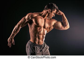 sportsman - Handsome muscular bodybuilder posing over black...