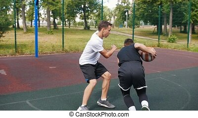 Sportsman in black uniform playing basketball on the court outdoors with friend, dribbling and missing past the basket